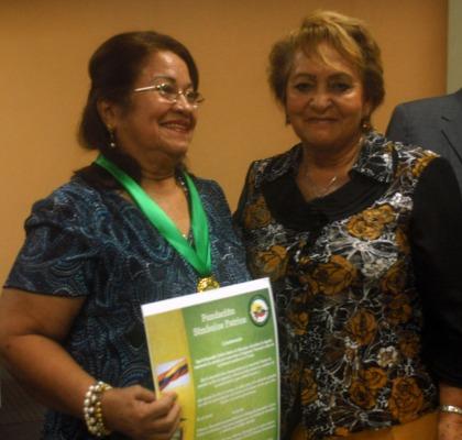 Laura Zambrano (d), miembro de la Fundación Símbolos Patrios, luego de entregar la medalla y el acuerdo que declaran Maestra Ejemplar a Carlota Suárez de Manrique.