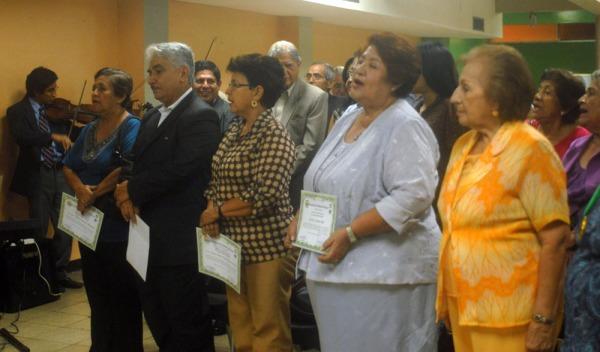 Teresa Cadena de Santander (i), Leonardo Torres, Matilde Barros y Carmen Albán, docentes homenajeados, cantando el Himno al Maestro.